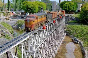 A model train running on a bridge in a garden railroad