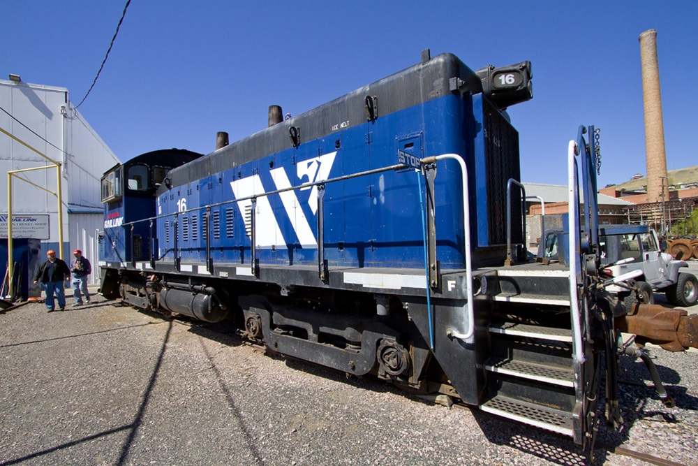 Blue switching locomotive viewed up close with a wide-angle lens.