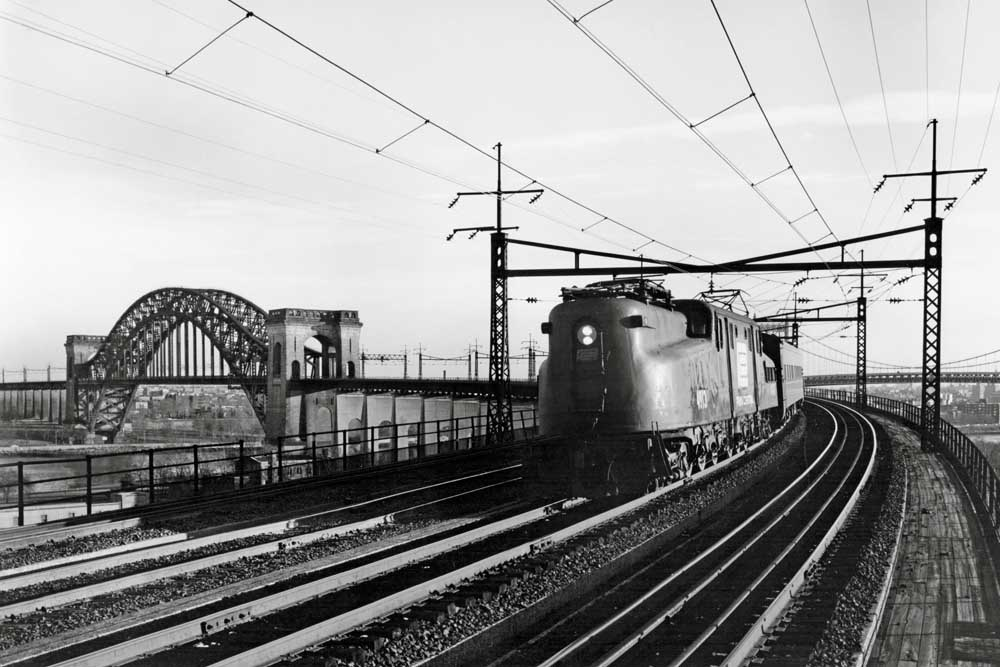 Electric locomotive brings passenger train around curving bridge