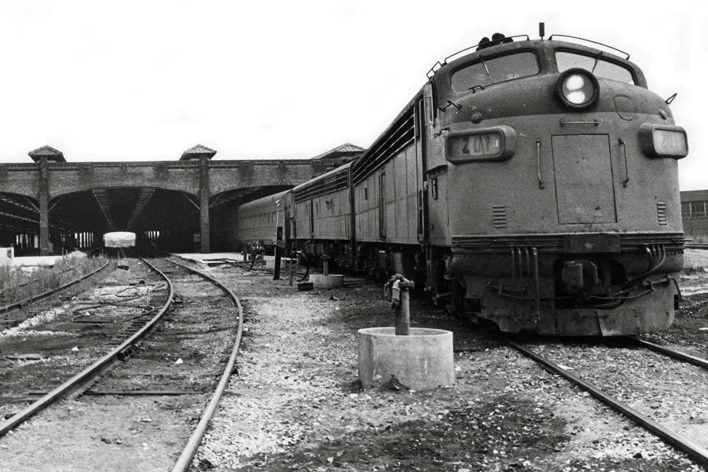 Diesel locomotive with passenger train sticking out of building