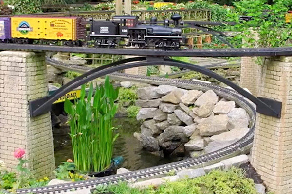 a garden railway showing a steam locomotive on a bridge over a pond and rocks