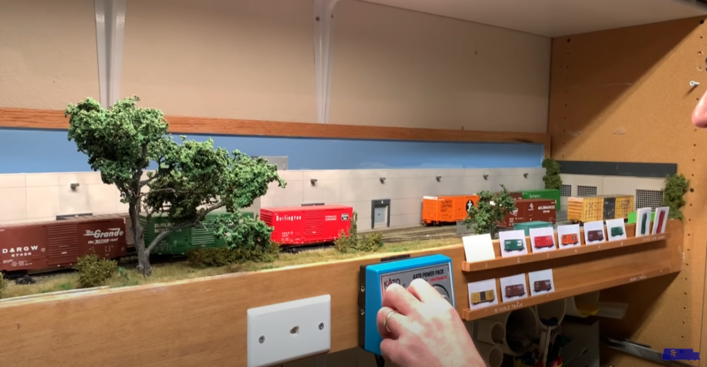 Hand operating a switching model train layout