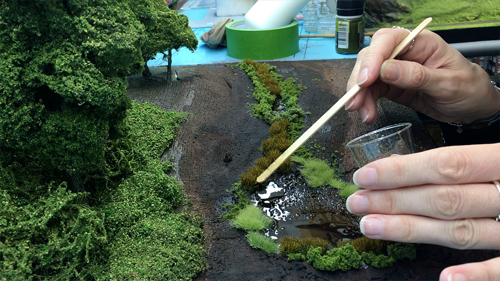 Someone applying glue to place down grass on a layout