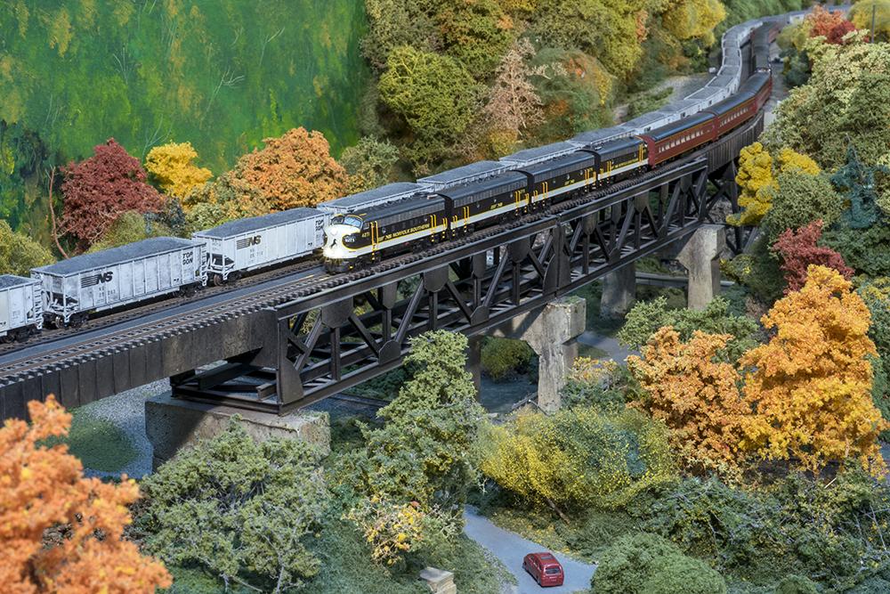 A model train on a bridge with fall scenery underneath