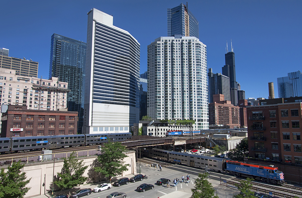 A major metropolitan city with a couple of diesel trains by tall buildings