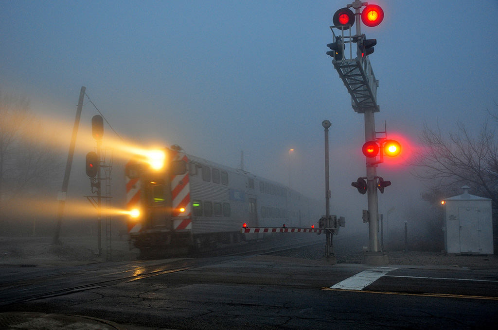 A metra train passing through a stop light