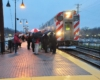 Passengers waiting in the rain to board the metra