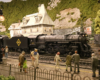 A 4-6-2 steam locomotive model pulls a train through the center of a town in a mountainous and forested scene.