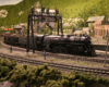 A 4-8-4 steam locomotive leads a freight train through an S-curve in a mountainous and forested scene and past several railroad and industrial buildings.