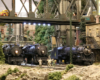 Three model steam locomotives pause in an industrial scene surrounded by trees.