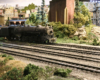A 2-10-2 model steam locomotives on yard tracks amid a verdant industrial scene.