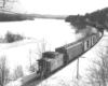 a freight train going off into the distance with a caboose in the foreground on a winter day
