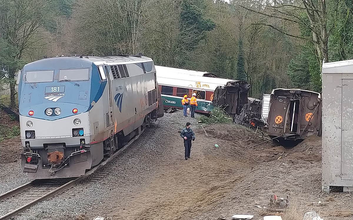 Locomotive stopped on tracks with derailed cars in background