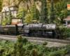 A 2-8-4 steam locomotive runs through a verdant, rocky scene.