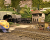 A model steam locomotive exits a tunnel into a rail yard. A blue and yellow diesel locomotive sits in the foreground.