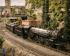 A 4-6-2 model steam locomotive pulls a passenger train from a yard around a curve in a verdant town scene. A rail yard with road bridge, signals, and additional steam trains are in the middle and background.