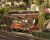 A model 2-8-8-4 steam locomotive pulls a train over a brick viaduct in the background of a verdant city scene.