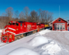 A red train passing by a snowy depot