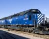 A blue train sitting on the tracks