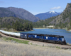 A blue train turning a corner by a body of water with mountains in the background