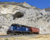A blue train passing by a rocky mountain