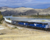 A blue train turning a corner next to a body of water