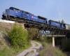 A blue train passing over a bridge