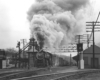 a steam engine pulling freight with a huge plume of smoke