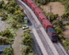 A red express freight train with a caboose on the rear pass through a small town near a river.