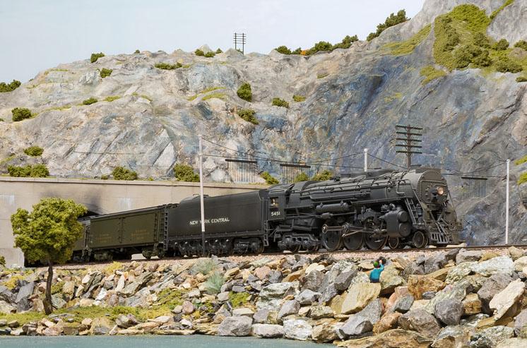 A model steam locomotive leads an express train through a mountainous scene.
