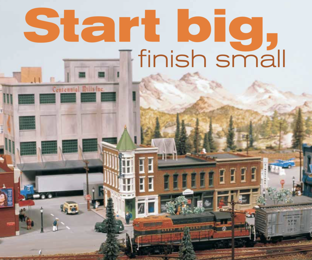 Picture of an N scale small town with a GP7 Great Northern unit in the foreground and an industrial building in the background. The original headline appears in the sky: Start Big, Finish Small.