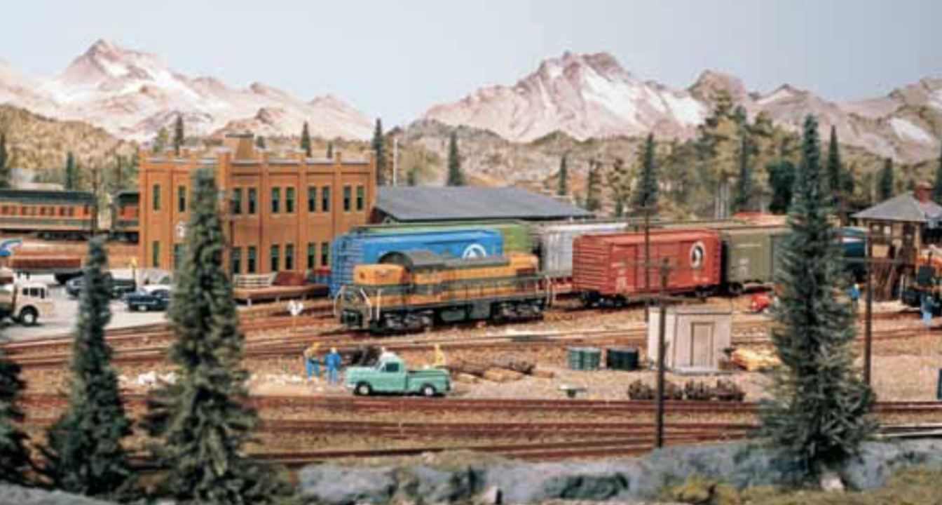 A different view of the layout through evergreen trees and focusing on a Great Northern painted locomotive, likely a GP7.