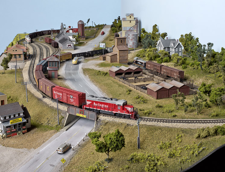 an HO scale layout with a red diesel pulling boxcars