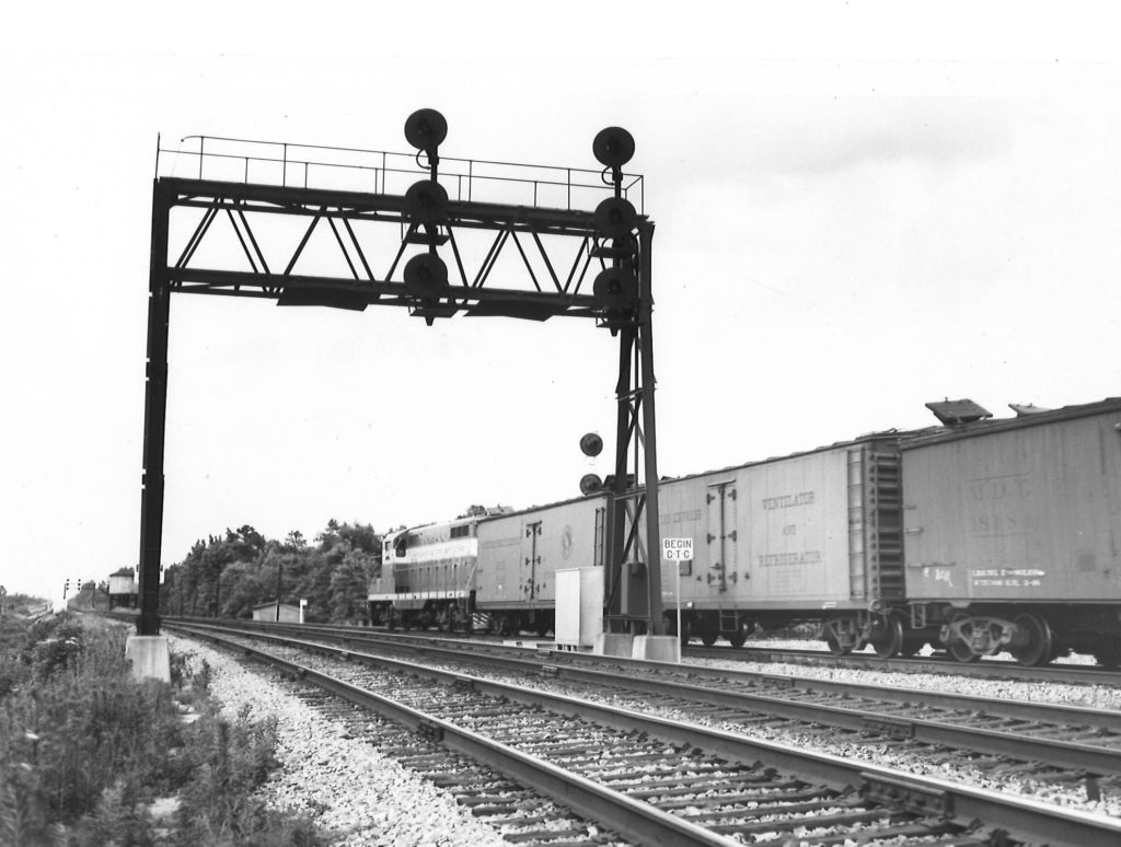 A black and white photo taken from behind a GP7 diesel locomotive as it passes by a stop light