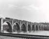 A black and white distant shot of a steam locomotive crossing a bridge