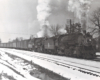 A black and white photo of a steam locomotive on a snowy day