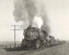 A black and white close up photo of a steam locomotive with white and gray smoke coming out of its chimney