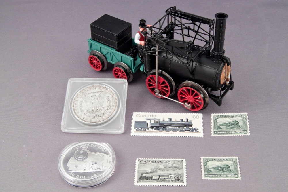 A model of an early looking toy train, an old U.S. silver dollar, a Canadian coin, and postage stamps from Canada.