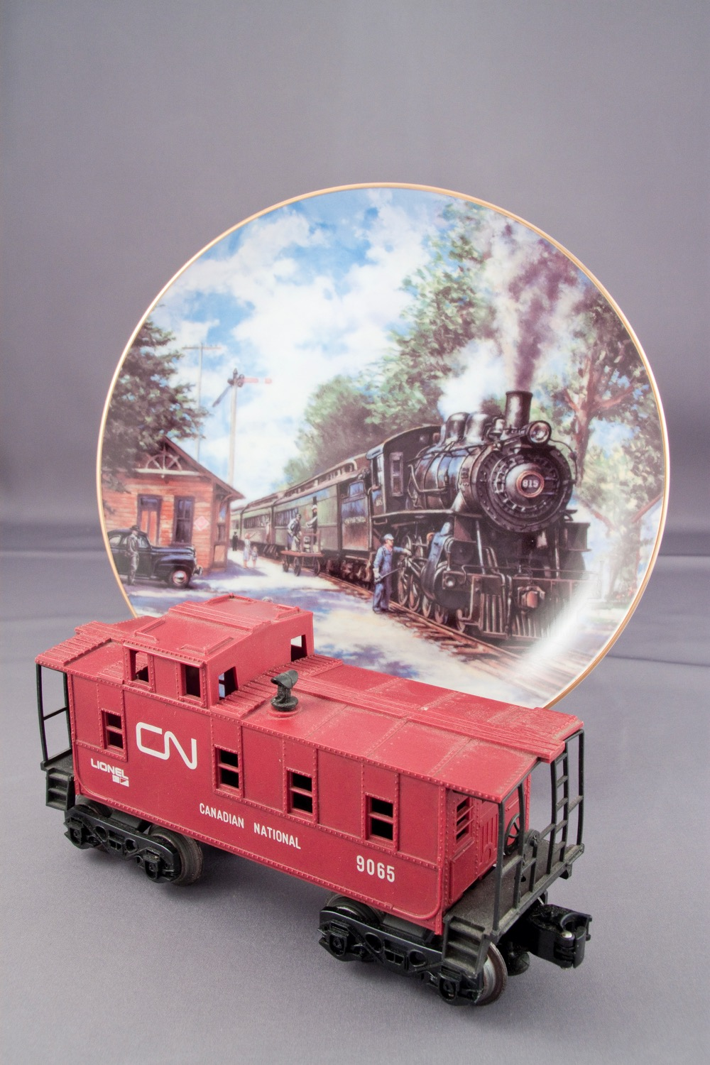 A collector's plate featuring a steam locomotive-hauled train and a Lionel-made Canadian National branded caboose.