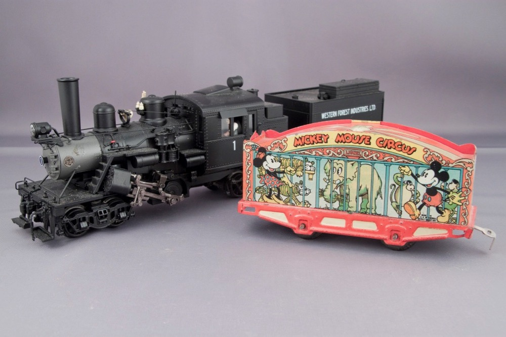A detailed Climax logging locomotive model next to an old-looking circus car with few details and printed sides showing a caged elephant and Mickey and Minnie Mouse.