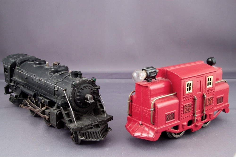 A black-colored Lionel steam locomotive is on the left, with a red Dorfan locomotive on the right looking like an early 1900s electric freight motor.