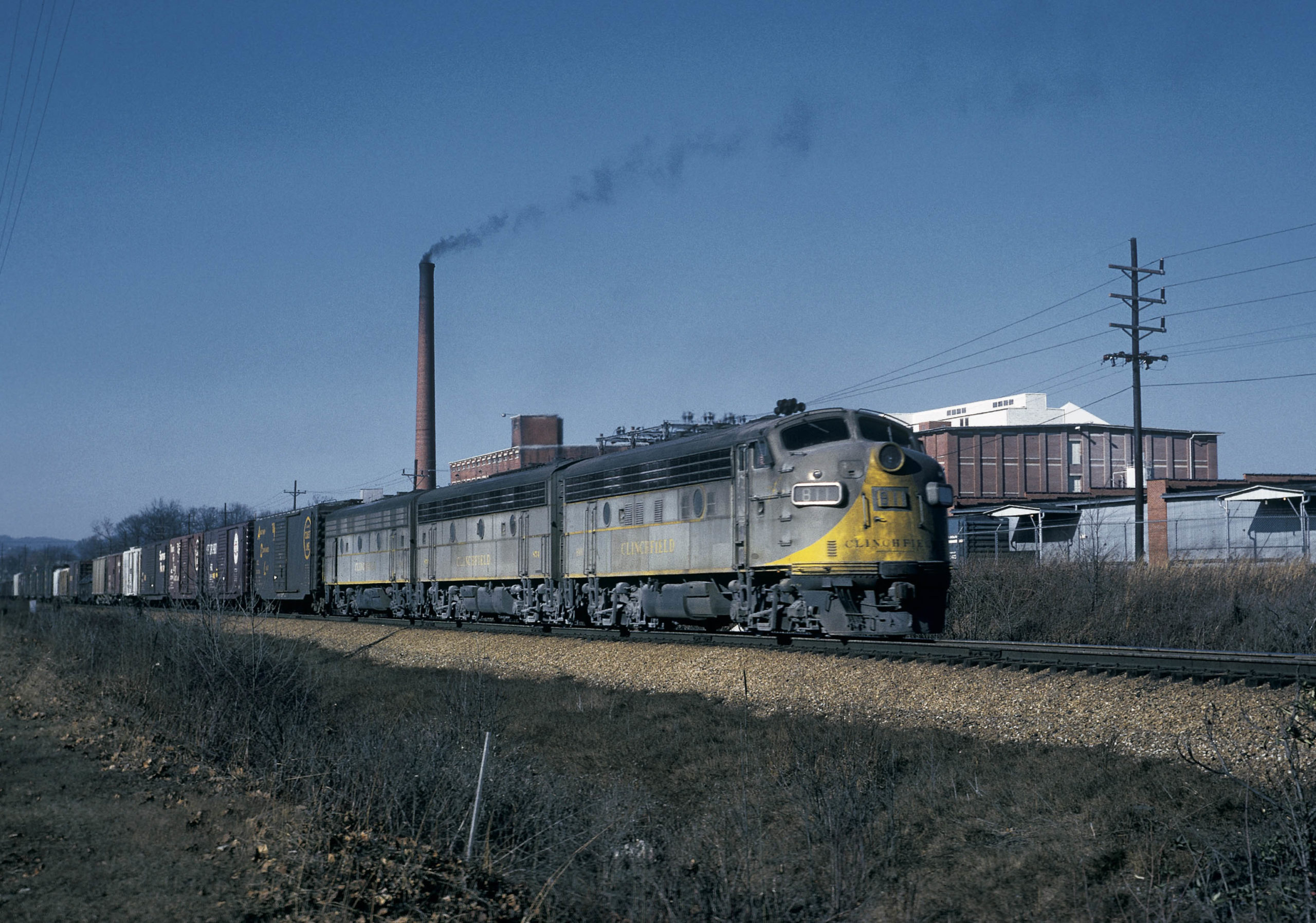 Southbound manifest train 26, three F unit diesels, pauses by the Borden Textile Mill in Kingsport, Tennessee, in March 1967 to add a three-unit rear-end pusher for the 42-mile climb to Erwin.