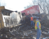 Workers examining a derailed train