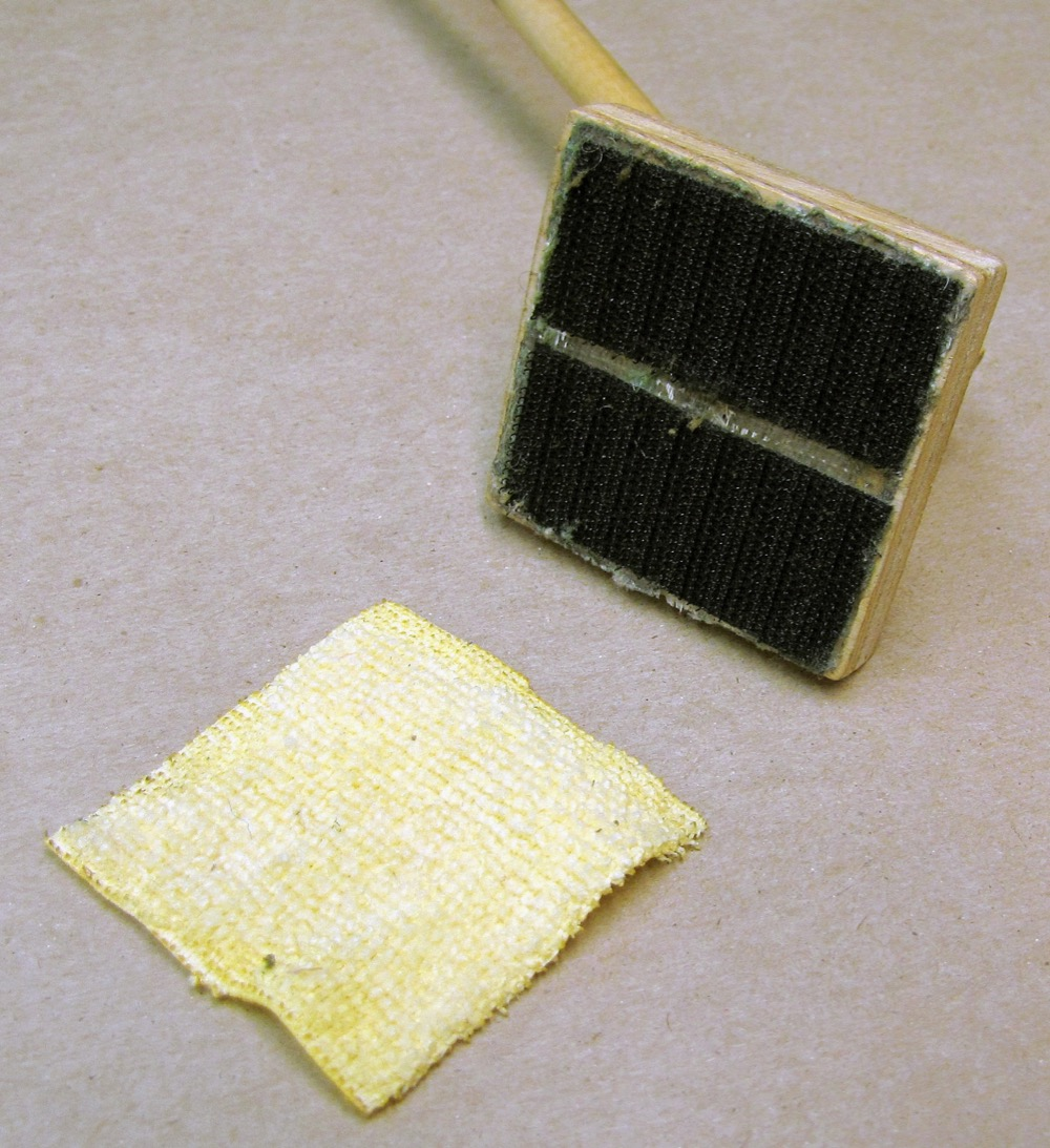 Showing the underside of the track cleaning tool with cleaning pad separate from velcro.
