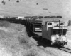 A black and white picture of a caboose transporting vehicles