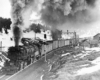 A black and white photo of a 2-8-8-2 steam locomotive turning the corner on the tracks with a lot of smoke coming out of its chimney