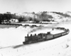 A black and white photo of a 2-8-2 steam locomotive turning the corner on the tracks on a snowy day