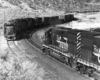 A black and white photo of two diesel locomotives passing each other on the tracks