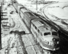 A black and white diesel locomotive on the tracks on a snowy day