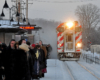 Passengers waiting outside in the snow for a train